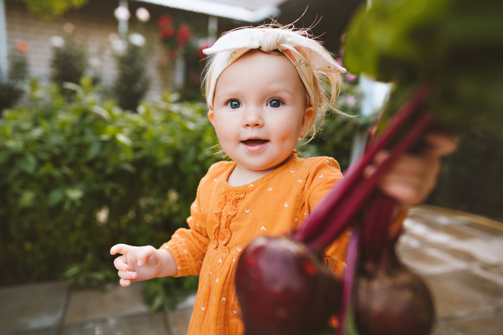 baby-holding-healthy-plant-based-food